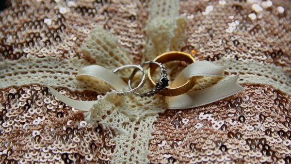 TJ And Sinead's Wedding Rings on bronze sequin with lace ribbon