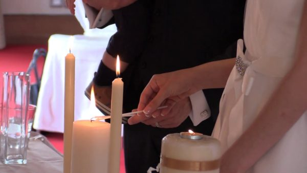 Ana Paula and Darren lighting the wedding candle together